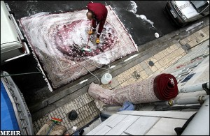 Man washing carpets just outside his house.